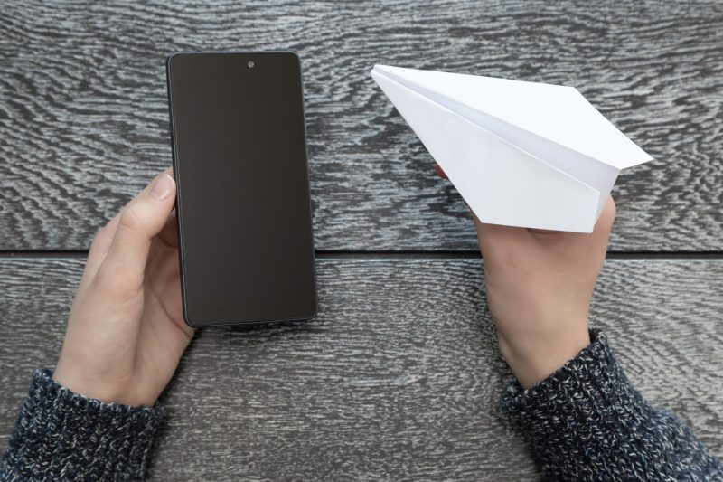 the-girl-is-holding-a-white-paper-plane-and-a-swit-GCHB9LN